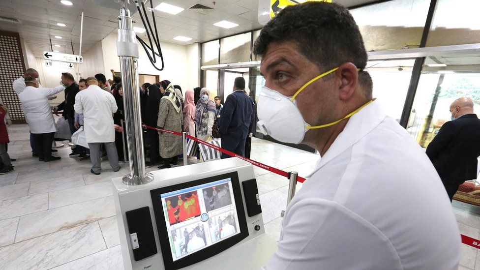 Members of Iraqi medical team check passengers upon arrival from Iran at Baghdad international airport