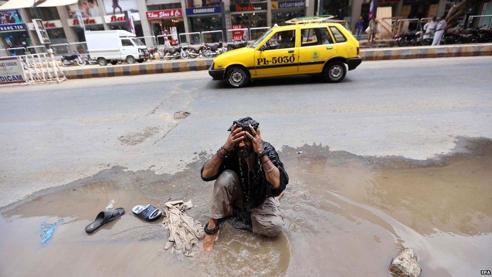 A Pakistani attempts to cool off in a puddle on a roadside in Karachi, Pakistan, 25 June 2015.