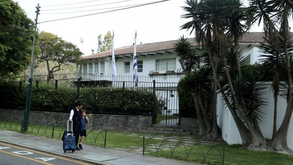 A woman and a child walk outside the residence of the Uruguayan ambassador in Peru