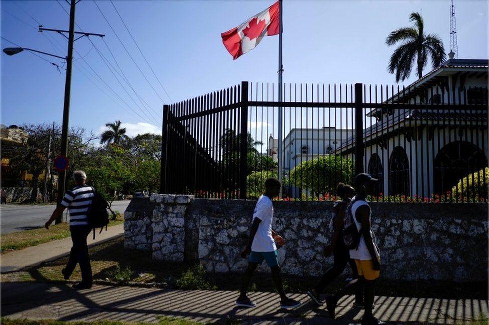 People walking past the Canadian embassy in Havana