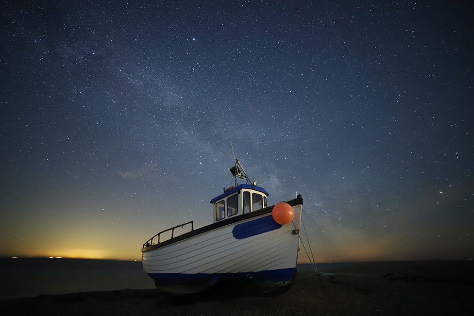 A fishing boat seen on the water beneath a night sky