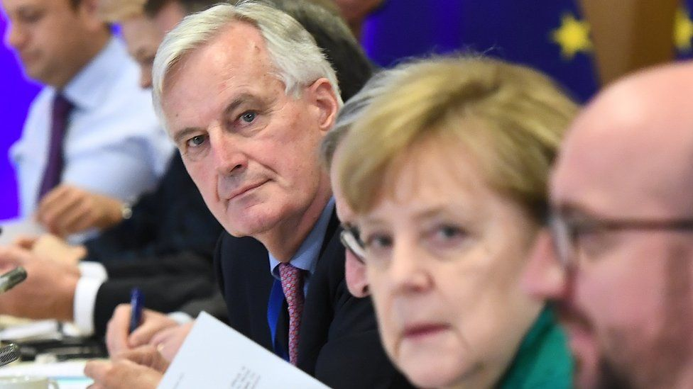 Chief Brexit negotiator Michel Barnier, centre, looks at the camera, as does German Chancellor Angela Merkel (in slightly soft focus)
