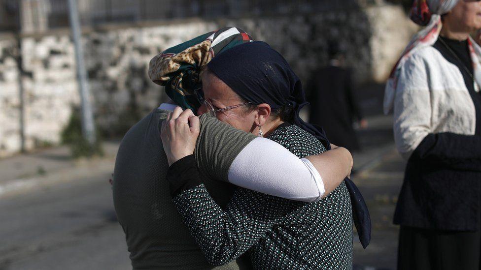 Mourners hug