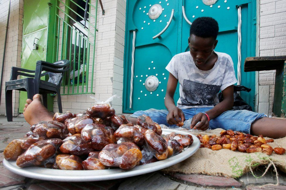 A boy bags dates in front of a mosque in Abidjan, Ivory Coast, on 24 April.