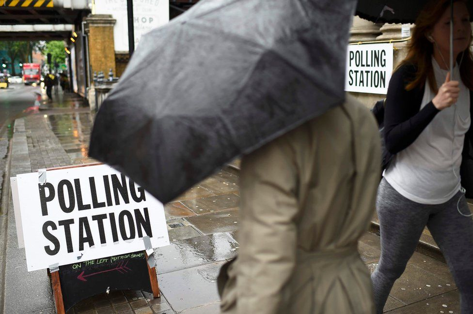 Pedestrians carrying umbrellas during heavy rainfall pass a polling station, on the day of the EU referendum, in central London