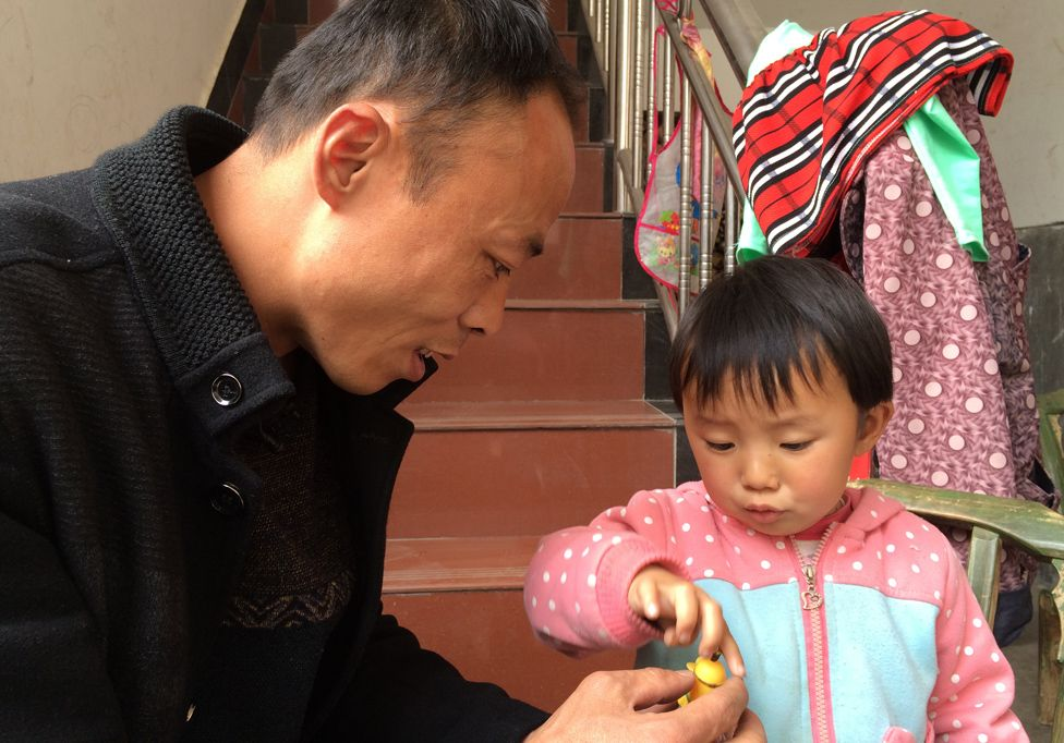 Family planning officer Li Bo plays with two-year-old Liu Siqi