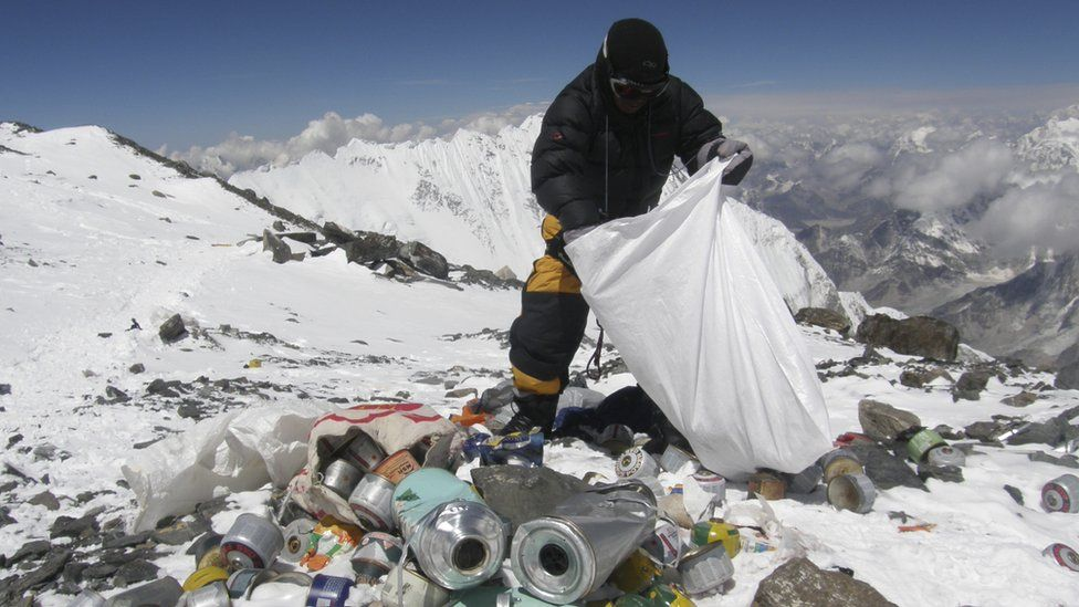 This picture taken on May 23, 2010 shows a Nepalese sherpa collecting garbage, left by climbers, at an altitude of 8,000 metres during the Everest clean-up expedition at Mount Everest. A group of 20 Nepalese climbers, including some top summiteers collected 1,800 kilograms of garbage in a high-risk expedition to clean up the world's highest peak
