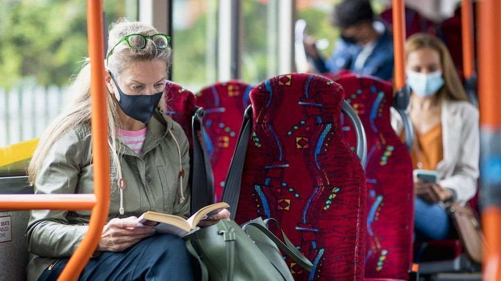 Woman sitting on a bus wearing a protective mask during the Covid-19 pandemic