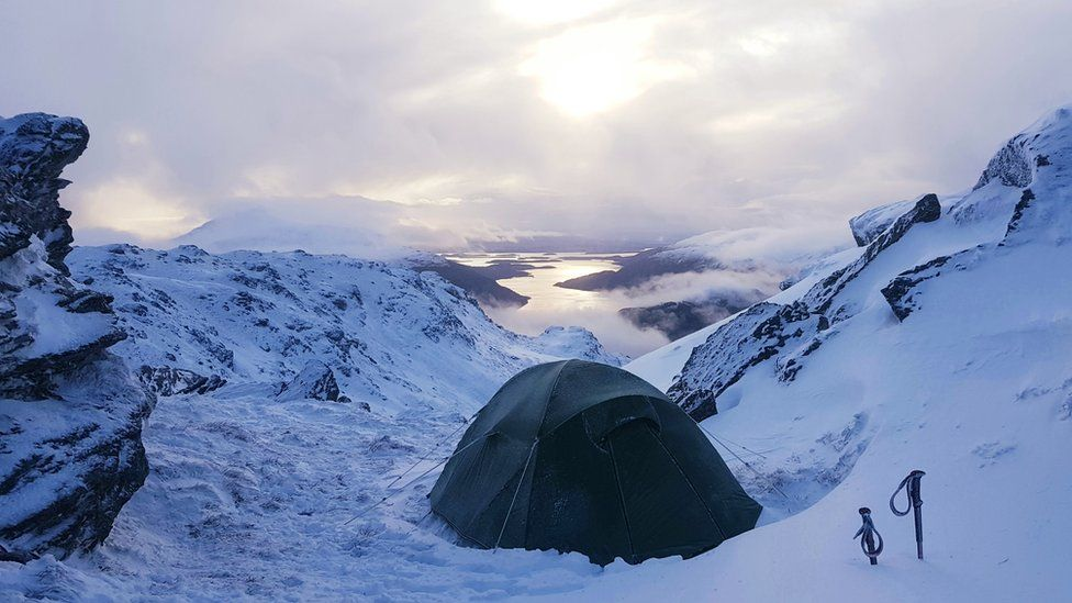 Tent on a snowy mountainside with loch in valley below