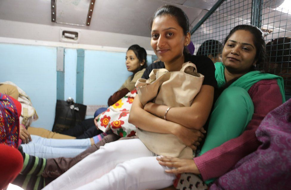 Pallavi (in green) sits with another woman on her lap