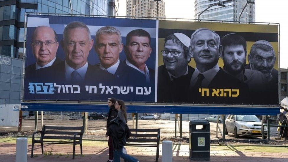Israelis walk past billboards put up by the centrist Israeli Blue and White alliance parties featuring their candidate for Prime Minister, Benny Gantz, alongside a panel showing the Likud party (R) with Prime Minister Benjamin Netanyahu and extreme right-wing members of the Likud party, in Tel Aviv's diamond district, 15 March 2019