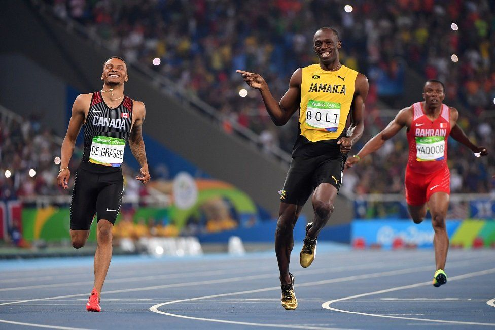 Jamaica's Usain Bolt (C) jokes with Canada's Andre De Grasse (L) after they crossed the finish line in the Men's 200m Semifinal during the athletics event at the Rio 2016 Olympic Games at the Olympic Stadium in Rio de Janeiro on 17 August, 2016