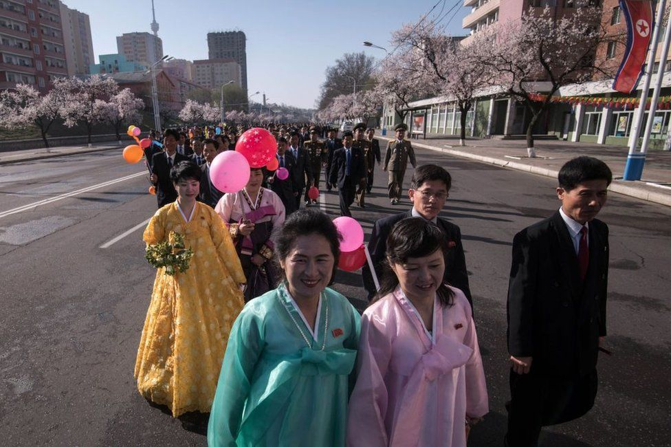 Attendees wearing traditional Korean dress make their way to the opening ceremony for the Ryomyong Street housing development in Pyongyang on 13 April 2017.
