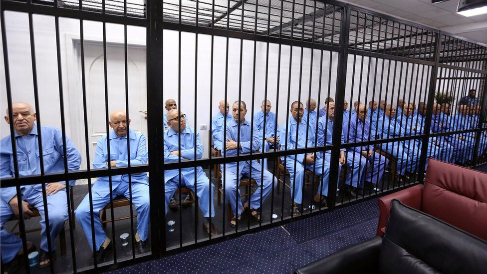 Gaddafi's former aides sit dressed in prison blue behind the bars of the accused cell during their trial at court of appeals in the Libyan capital, Tripoli.