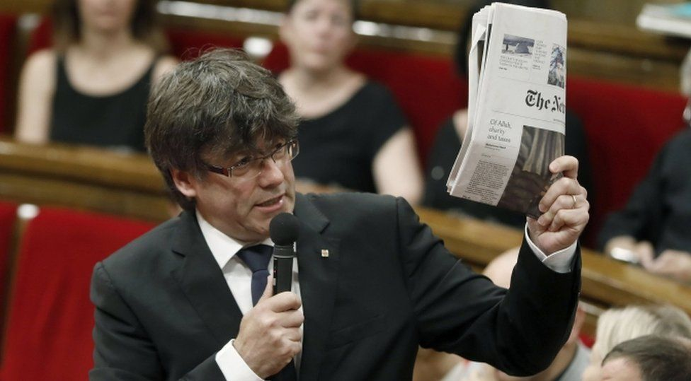 Spain's Catalonian regional president, Charles Puigdemont, holds an issue of the New York Times with an article on Catalonia's independence referendum, during question time at the regional Parliament in Barcelona, Spain, 28 June 2017.