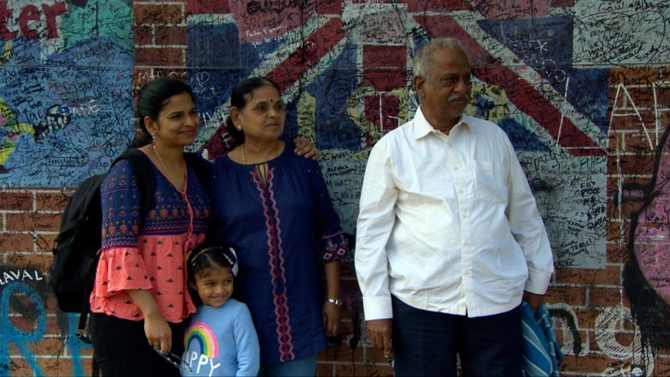 A family visit a Belfast peace wall