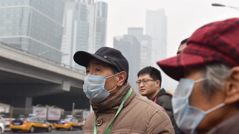 People wear masks while waiting for a bus on a polluted day in Beijing on February 27, 2018