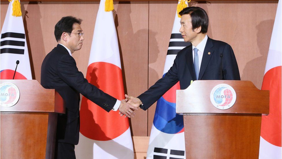 Japanese Foreign Minister Fumio Kishida (left) and South Korean counterpart Yun Byung-Se (right) shake hands during a joint press conference on 28 December