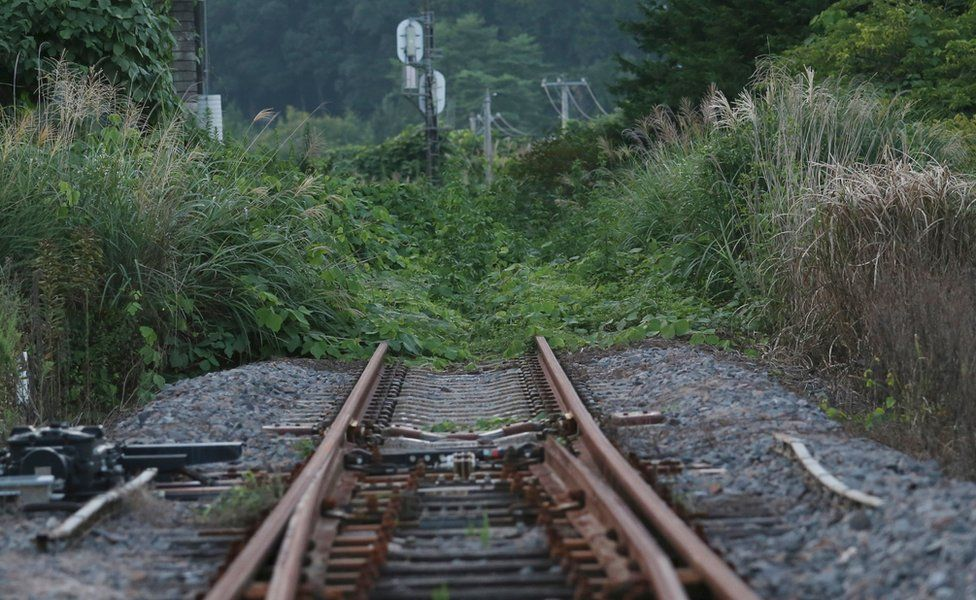 The rusty train track of the Joban line is covered with weeds near Tatsuta Station in Naraha town - the first of seven evacuated towns to reopen since the 2011 disaster
