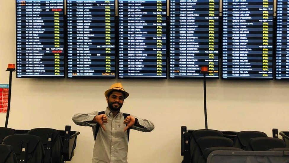 Khalid poses in front of departure boards