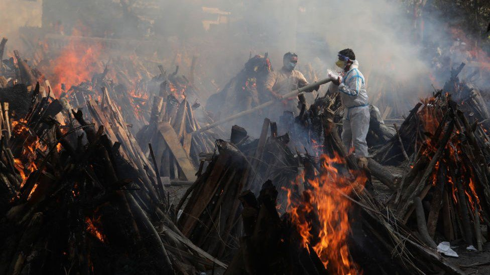 Relatives stand next to the burning funeral pyres of those who died due to the coronavirus disease (COVID-19), at Ghazipur cremation ground in New Delhi.