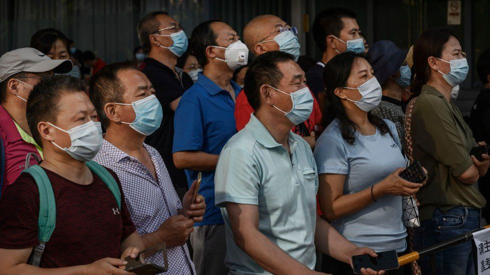 Chinese parents and relatives watch as students, not seen, leave a school after taking the National College Entrance Examination,