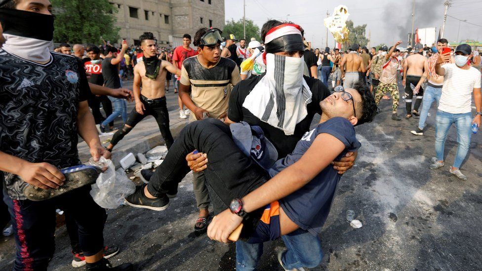 A man carries away an injured protester in Baghdad, Iraq (2 October 2019)