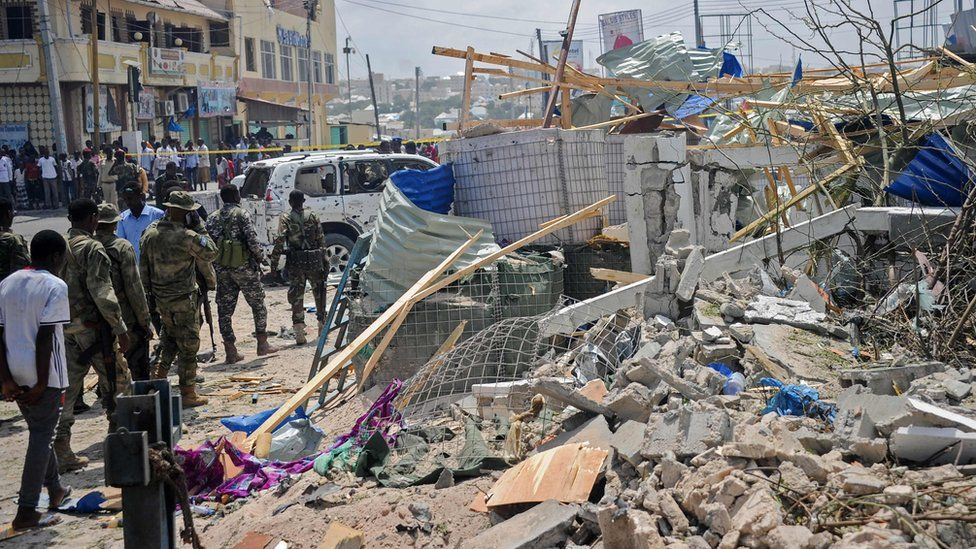 Somali security force personnel walk among debris at the site of a car bomb explosion near the building of the Interior Ministry in Mogadishu on July 7, 2018.