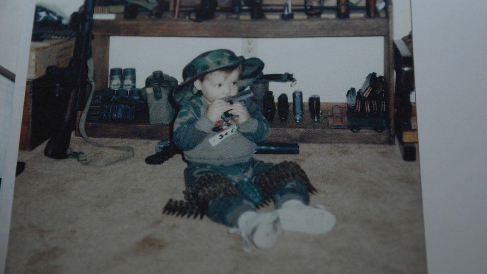 A photograph of a toddler sitting surrounded with weapons
