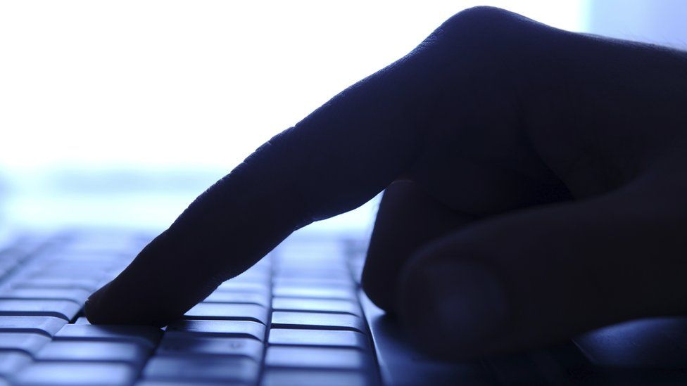 Finger pressed down on computer