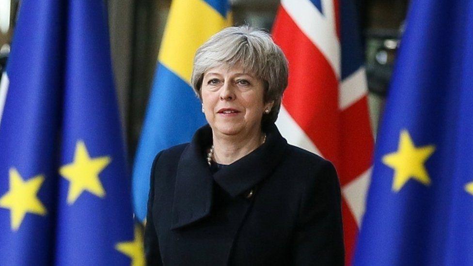 Theresa May standing amongst EU flags