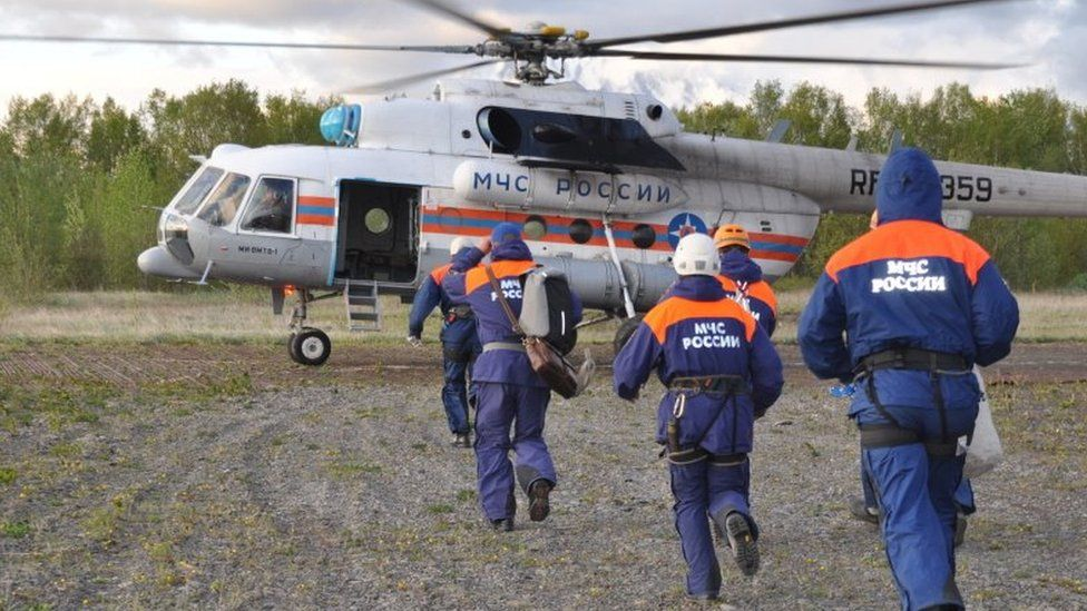 Russia's emergencies ministry rescuers run to a helicopter. File photo
