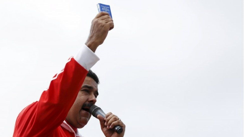 Venezuela's President Nicolas Maduro holds a copy of the country's constitution while he talks to supporters during a meeting outside Miraflores Palace in Caracas, December 15, 2015.