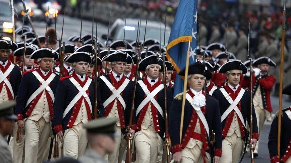 Participants march in period costumes on Pennsylvania Avenue