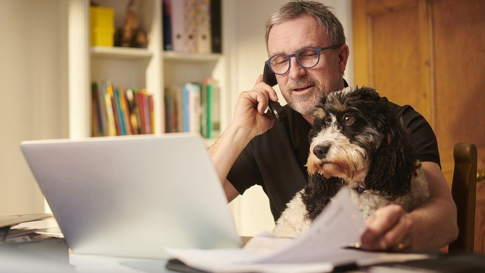 A man is on the phone, petting his dog while also surveying assorted papers scattered around his open laptop