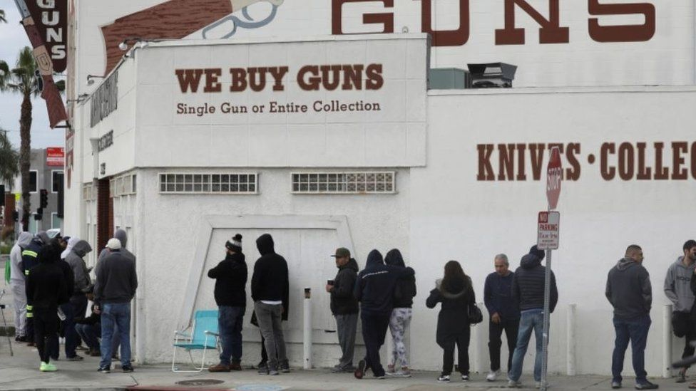 People wait in line outside to buy supplies at a gun store in Culver City, California,