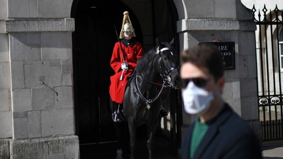 A man wearing a protective face mask walks past a member of the household cavalry on Whitehall