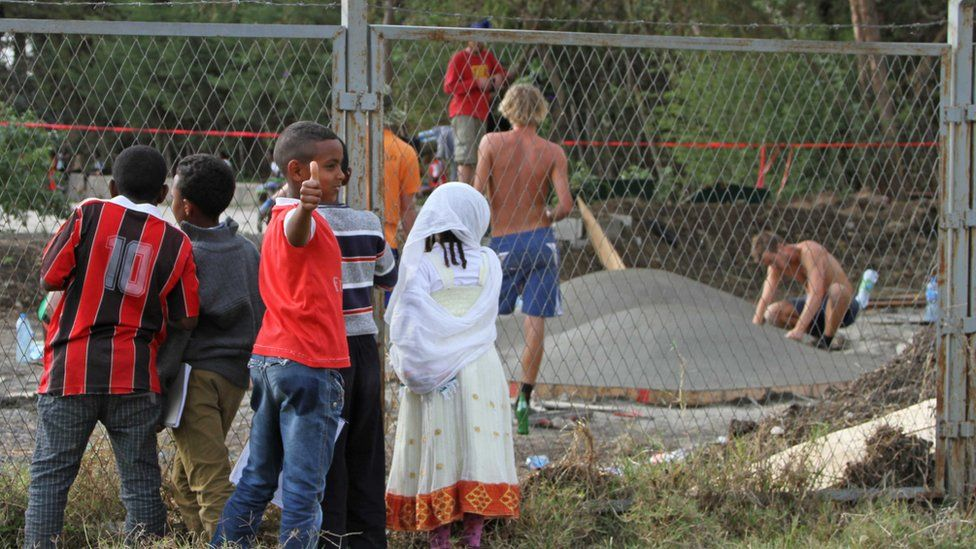 young children look on from outside the skatepark fence at the construction going on