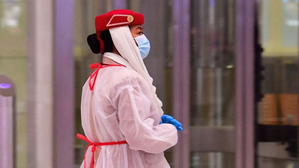 Am airline staffer (In July) wearing protective gear looks on as tourists get a medical screening upon arrival at Terminal 3 at Dubai airport, in the United Arab Emirates