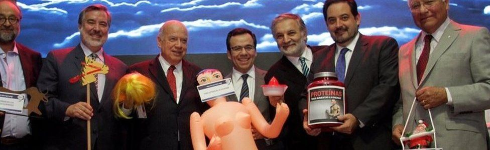 """Chile's economy minister Luis Cespedes (C) holds up an inflatable doll during an event of the exporters"""" association Asexma in Santiago, Chile, December 13, 2016"""