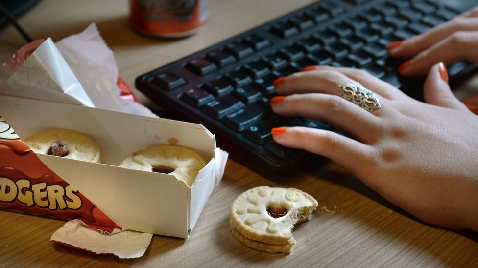 Woman eating biscuits at desk