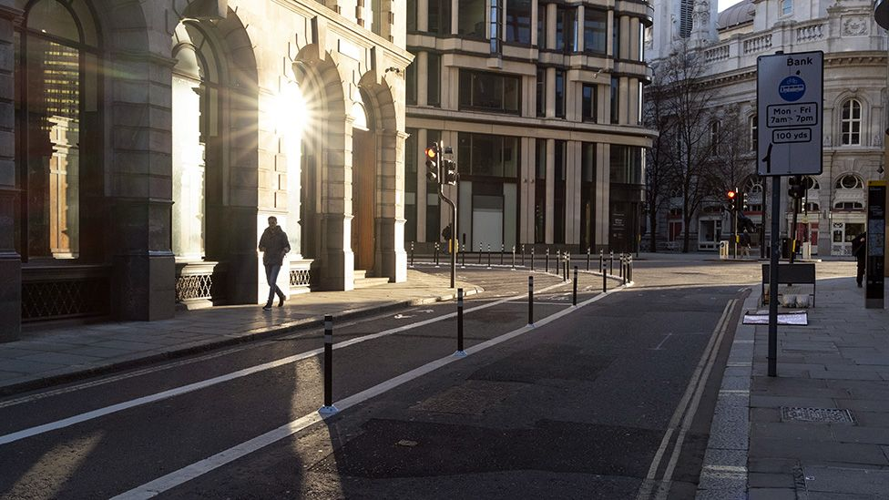 A lone commuter walks on a widened Old Board Street pavement at evening rush-hour in the City of London on 26 February