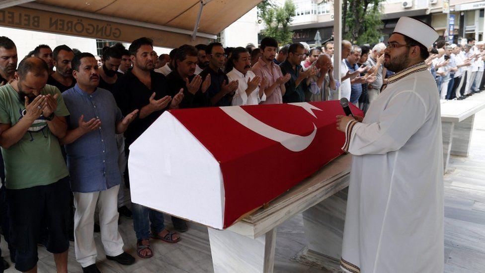 Relatives of Siddik Turgan, a customs officer at Ataturk airport, attend his funeral