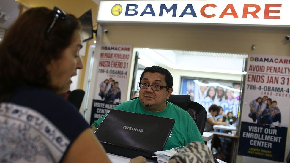 An insurance agent helps a Miami, Florida, woman pick out her health care plan