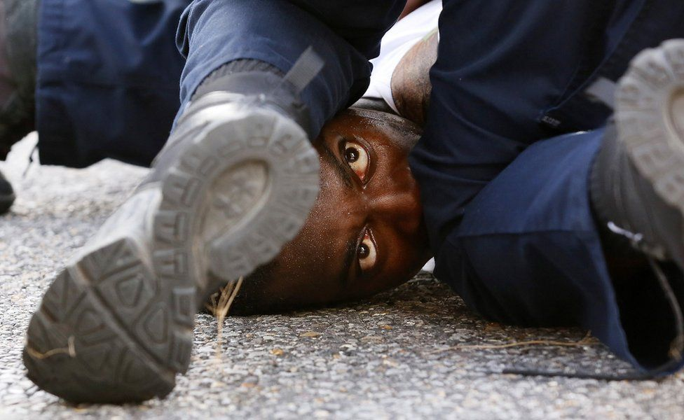A man protesting the shooting death of Alton Sterling is detained by law enforcement near the headquarters of the Baton Rouge Police Department in Baton Rouge, Louisiana, U.S. July 9, 2016