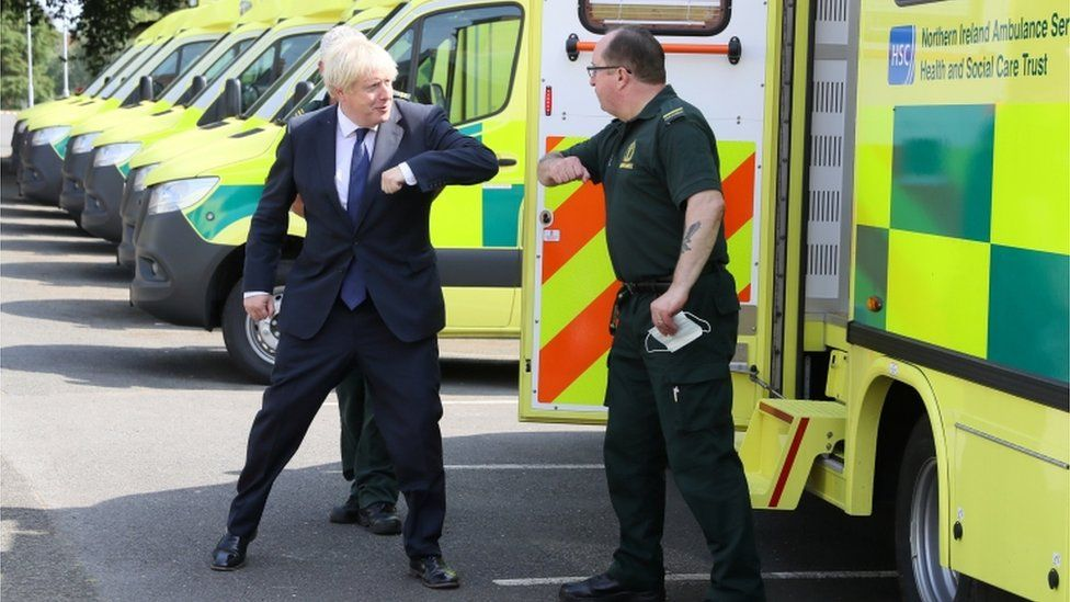 Britain's Prime Minister Boris Johnson elbow bumps a paramedic at the Northern Ireland Ambulance Service HQ during his visit to Belfast
