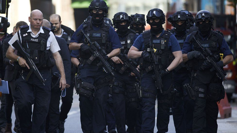 Armed police officers patrol London's Borough Market on the morning after Saturday's attacks