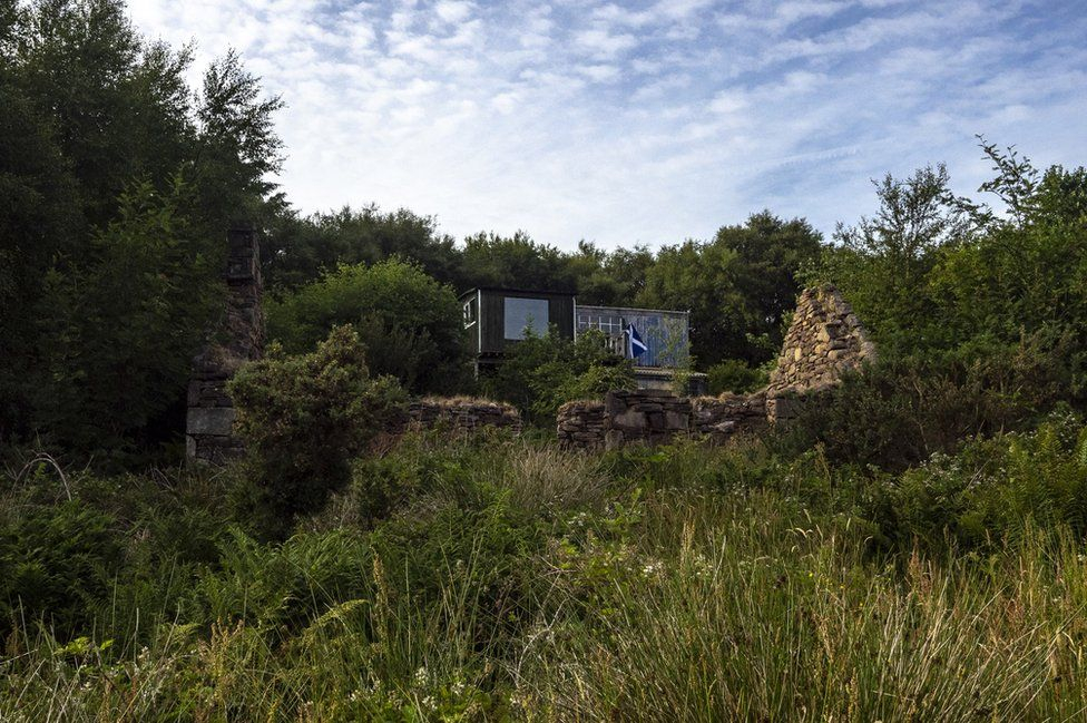 Ruins of a former croft in front of a current residence