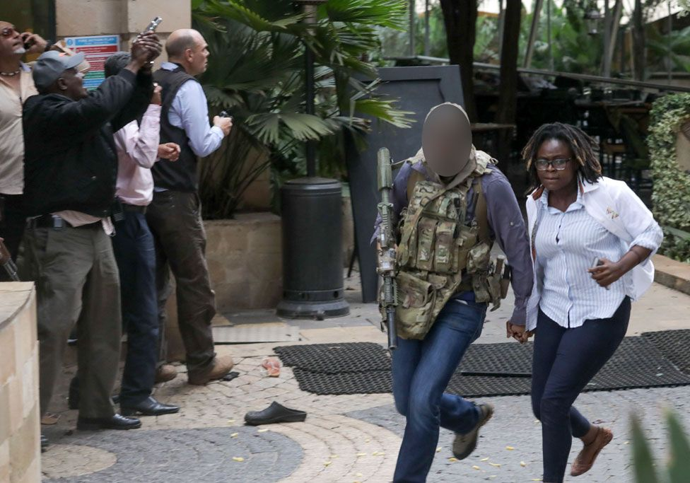 A man believed to be a member of the British SAS helps a woman caught up in the attack to safety