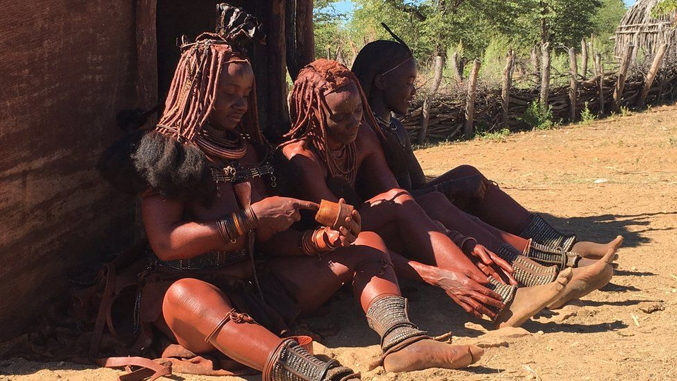Himba women applying red-coloured ochre on their skin as a daily beautification ritual in Kunene region, Namibia